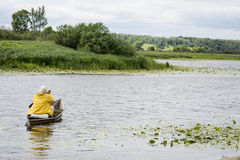 In summer, the woman fisherwoman boat floats on the river with a Stock Photos