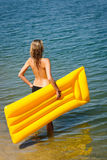 Summer woman hold yellow floating mat Royalty Free Stock Photo