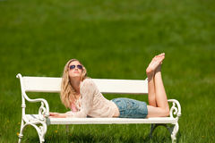 Summer - Woman lying on bench in meadow Stock Photo