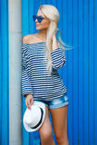 Summer woman portrait on blue background. The young beautiful woman, the blonde with a long straight hair and blue eyes, an easy make-up, is dressed in a sea royalty free stock photo