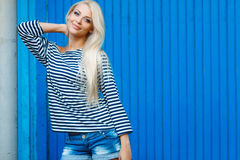 Summer woman portrait on blue background. The young beautiful woman, the blonde with a long straight hair and blue eyes, an easy make-up, is dressed in a sea stock photography