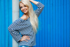Summer woman portrait on blue background. The young beautiful woman, the blonde with a long straight hair and blue eyes, an easy make-up, is dressed in a sea stock photo