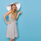 Summer Woman In White Sun Hat Is Laughing And Pointing. Beautiful young woman in white dotted summer dress and sun hat is pointing, looking at camera and Royalty Free Stock Images