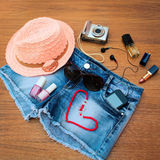 Summer women's accessories: red sunglasses, beads, denim shorts, mobile phone, headphones, a sun hat, camera, nail polish, Royalty Free Stock Photography