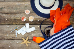 Summer women's beach accessories for your sea holiday and pill. On old wooden background. Concept of medication required in journey Stock Images