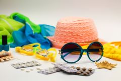 Summer women`s beach accessories for your sea holiday and pill on white background. Concept of medication required in journey royalty free stock images