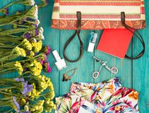 Summer women set with straw bag, dress, colorful flowers, cosmet. Travel concept - summer women set with straw bag, dress, colorful flowers, cosmetics makeup Stock Image