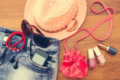 Summer womens accessories. Sunglasses, beads, denim shorts, mobile phone. Toned image Royalty Free Stock Photos