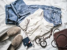 Summer womens fashion clothes set - mom`s jeans, suede sneakers, cotton t-shirt, bag, bracelets, lipstick on a light. Summer women`s fashion clothes set - mom`s stock photo