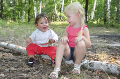 Summer in the woods on birch logs sits two little sisters Stock Photography