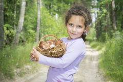 In the summer in the woods a little girl collected a basket of m stock photo
