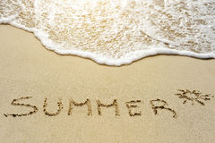 Summer word written on the sand beach Stock Images