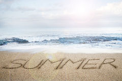 Summer word written on sand beach with sky clouds sunlight. Background Royalty Free Stock Photo