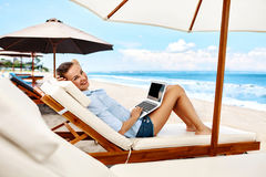 Summer Work. Woman Relaxing Using Computer On Beach. Freelance. Summer Work. Portrait Of Beautiful Happy Smiling Woman Relaxing On Sun Lounger, Using Laptop stock photography