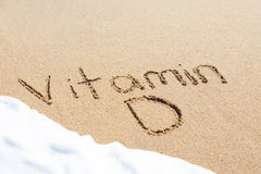 Summer written in the sand. With a foamy wave underneath Royalty Free Stock Photo