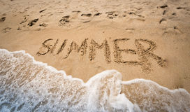 Summer written on wet sand at seashore Stock Image