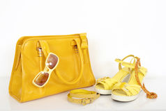 Summer yellow bag with matching sandals and accessories. Stock Photo