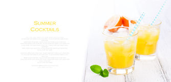 Summer yellow orange lemonade with ice and blood oranges and straw on a wooden table on a white background Royalty Free Stock Photos