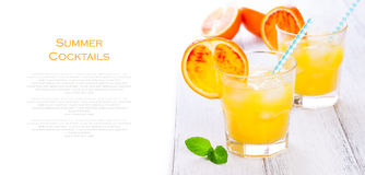 Summer yellow orange lemonade with ice and peaces of blood oranges and straw on a wooden table on a white background with place fo Stock Images