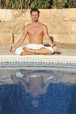 Summer yoga. Man by swimming pool in yoga lotus position Royalty Free Stock Photography