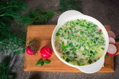 Summer yoghurt cold soup with radish, cucumber, and dill on wooden table. Okroshka.  Stock Photo