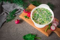 Summer yoghurt cold soup with radish, cucumber, and dill on wooden table. Okroshka.  Stock Photos