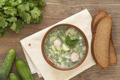 Summer yogurt cold soup with radish, cucumber, and dill on wooden table. Russian cold vegetable soup on yogurt. stock photo