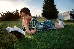 Happy woman lying on green grass reading a book in the park (outdoors). Summer. Young beautiful girl lying on the grass in a light summer dress and stock images