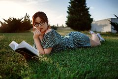 Happy woman lying on green grass reading a book in the park (outdoors). Summer. Young beautiful girl lying on the grass in a light summer dress and royalty free stock photography