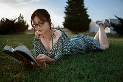 Happy woman lying on green grass reading a book in the park (outdoors). Summer. Young beautiful girl lying on the grass in a light summer dress and stock photos