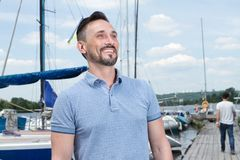 Summer Young cheerful bearded man relaxing on sailboat posing and looking at far on background of boats sky and folded wings stock photos
