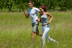 Summer - Young couple jogging in a meadow Stock Photography