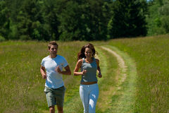 Summer - Young couple jogging in the meadow Stock Images