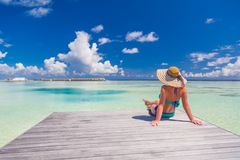 Beautiful attractive woman in bikini and hat lying on beach wooden jetty and luxury water villa. Sea view, luxury lifestyle Stock Images