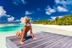 Perfect beach vacation for summer travel background. Relaxed woman wearing sun hat and bikini on a palm trees with the blue sea royalty free stock images