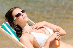 Summer young woman apply cream in bikini Stock Photos