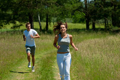 Summer - Young woman with headphones jogging royalty free stock images
