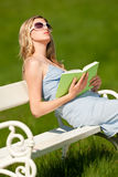 Summer - Young woman sitting on bench in meadow Royalty Free Stock Photo