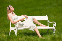 Summer - Young woman sitting on bench in meadow Royalty Free Stock Photography