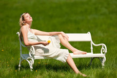 Summer - Young woman sitting on bench in meadow Royalty Free Stock Image