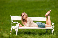 Summer - Young woman sitting on bench in meadow Stock Photography
