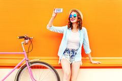 Summer young woman using taking self portrait on smartphone. With retro bicycle Royalty Free Stock Photos