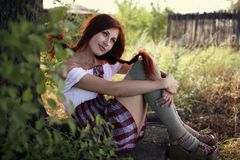 Summergirl. Red-haired girl with a sunflower near wooden fence stock photo