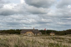 Summerhouse. Sommerhouse and Danish flag out the dunes a summer day Royalty Free Stock Photo