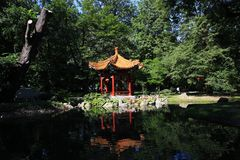 Chinese style summerhouse near pond. Summerhouse in Chinese style and bridge over pond in park Royalty Free Stock Photo
