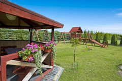 Summerhouse in a garden. Details of a wooden summerhouse for barbecue and relax in a garden with children's playground in a background Royalty Free Stock Photo