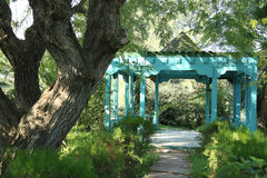 Summerhouse in the park. Summerhouse of blue color located in the park and surrounded by greenness Stock Images
