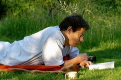 Summerly reading pleasure. Man with book and cup lies reading before a meadow Stock Image