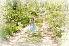 A summers day. A young girl walking along a nature path enjoying the first signs of Spring Royalty Free Stock Image