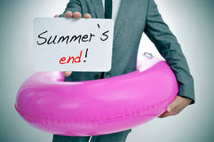 Summers end. Businessman with a pink swim ring showing a signboard with the text summers end written in it Royalty Free Stock Photo